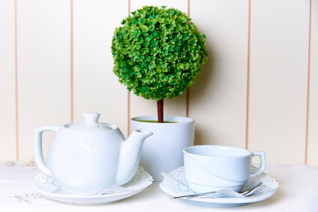 A white kettle and a cup on a saucer with lace next to a decorative tree in a pot.