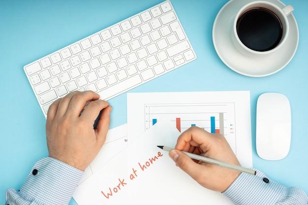 白いキーボードとマウス。テーブルにいる男性は、ドキュメントとチャートを扱います。リモートでの作業、自己隔離、自宅での作業、検疫。