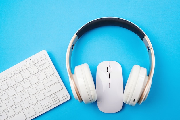 White keyboard, mouse and headphones on blue background, top view. copy space. remote education and work.