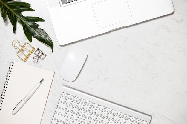 Белая клавиатура, мышь, канцелярские принадлежности, открытый красный карандаш для напоминания, зажим для папок и чашка кофе на мраморном столе