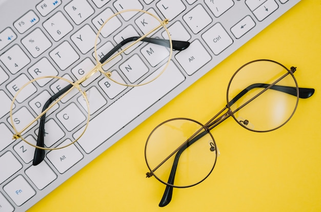 White keyboard and a pairs of glasses on yellow background