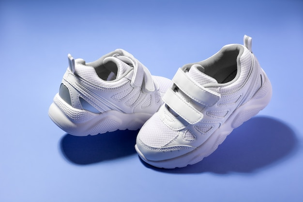 벨크로 패스너가 달린 흰색 아이 떠 있는 운동화는 보라색 배경 재치에 격리되어 서로 마주보고 있습니다.