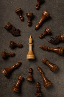 White king among black chess pieces on dark background