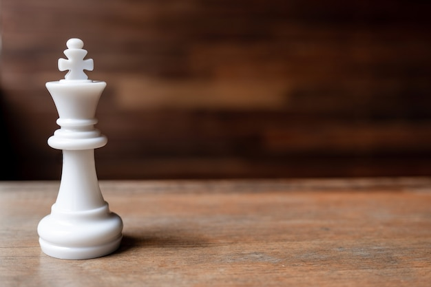 White king chess on wooden background challenge planning business strategy to success concept