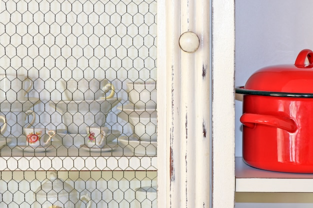 White kitchen cabinet shelf with also white tea and coffee cups, highlighting a red pot