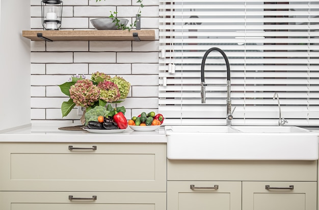 White kitchen cabinets with metal handles on the doors near the washbasin with a bouquet of flowers and a plate of vegetables.
