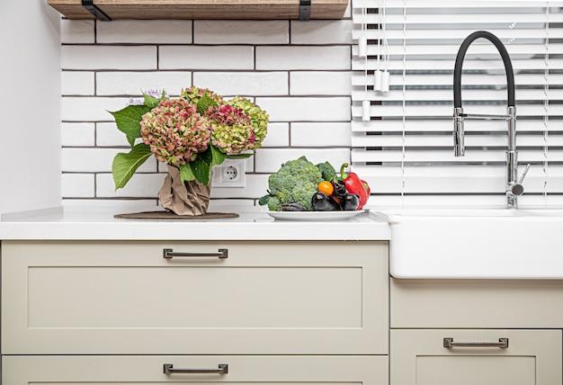 Белые кухонные шкафы с металлическими ручками на дверцах возле умывальника с букетом цветов и тарелкой овощей.