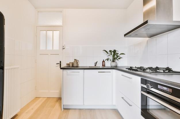 현대 아파트의 밝은 주방 문 근처에있는 가전 제품이있는 흰색 주방 찬장