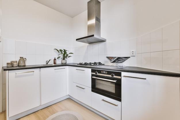 Белые кухонные шкафы с техникой, расположенные возле двери в светлой кухне современной квартиры