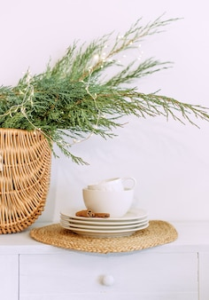 White kitchen set with cinnamon on a saucer and a basket with christmas needles