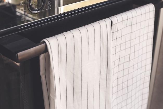 흰색 주방 수건이 오븐 손잡이에 달려 있으며 제품 모형