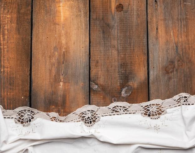 Белое кухонное полотенце на коричневом деревянном фоне, вид сверху, копия пространства
