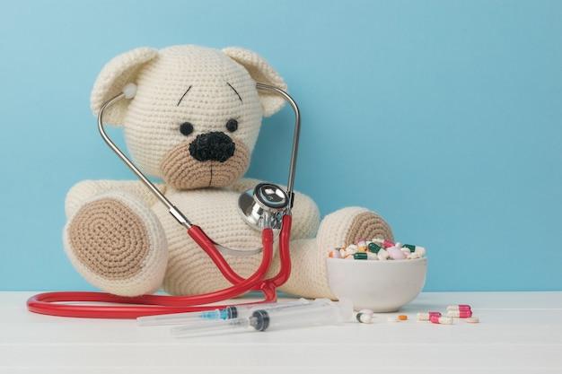 파란색 배경에 흰색 테이블에 의료 스타일의 흰색 니트 곰.