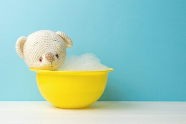 A white knitted bear in a yellow basin with a lot of foam.