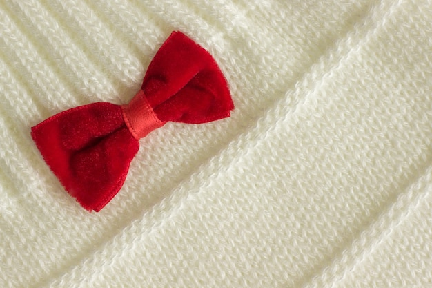 White knitted fabric with a red bow