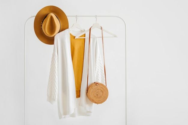 White knitted jumper on hanger with brown hat and bamboo bag