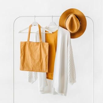 茶色の帽子と白い背景のエコバッグとハンガーの白いニットジャンパー。エレガントなファッション衣装。春のワードローブ。最小限のコンセプト。