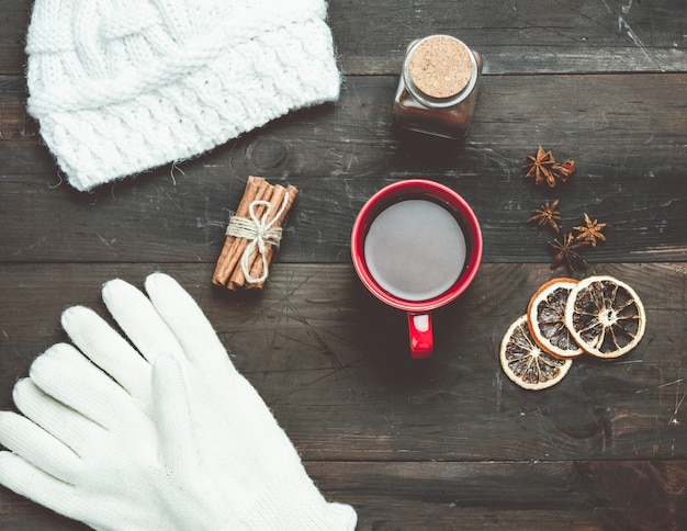 White knitted mittens and red cup with a drink on a brown wooden table, top view
