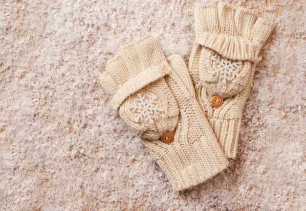 White knitted mittens in the snow