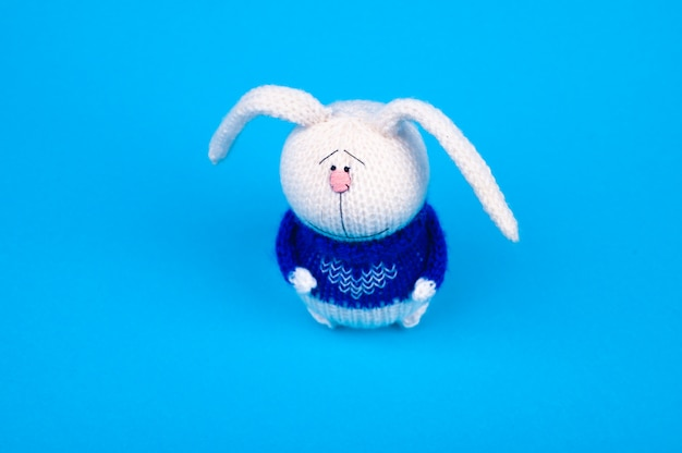 White knitted rabbit, in a blue jacket with a heart, on a blue background. rabbit with a heart. place for writing.