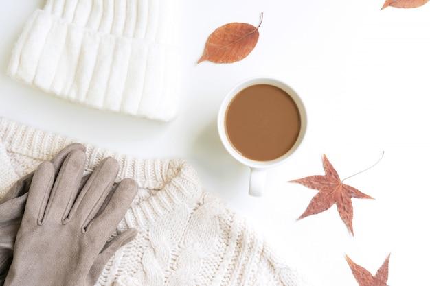 白いニットセーター、whool帽子、コーヒーカップ、手袋、乾燥したカエデの葉、白いblackground、フラットレイアウト、トップビュー、コピースペース