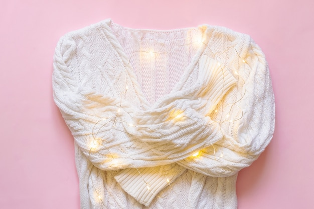 분홍색 배경에 크리스마스 빛 화환이 있는 흰색 니트 스웨터. 휴일 개념입니다.