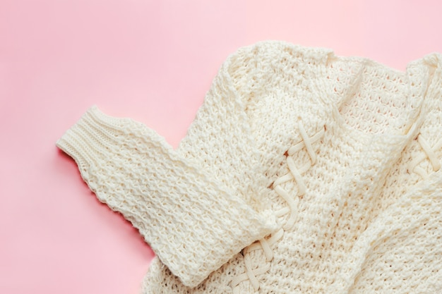White knitted warm womens sweater on a delicate pink background