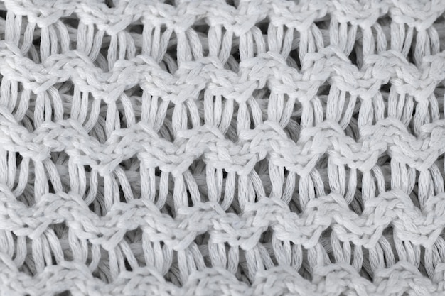 Белый вязаный шерстяной фон. вязаная теплая одежда для зимы текстура ткани