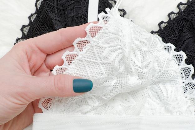 White lace bra in female hand. fashion concept
