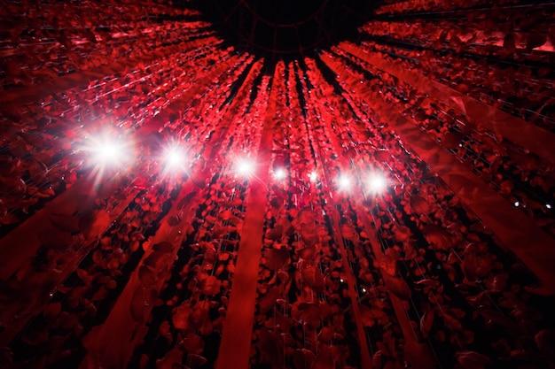 Белые лампы сияют сквозь нити с лепестками роз и красными лентами