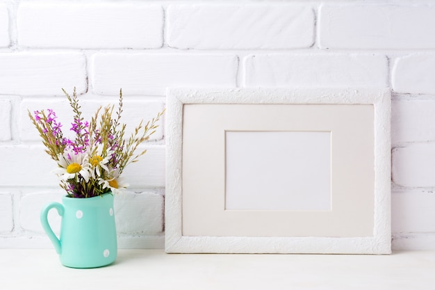 White landscape frame  with chamomile and purple flowers in mint green pitcher