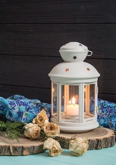 White lantern and dried roses with juniper branches. white candlestick on a wooden background