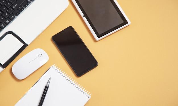 노란색 배경에 흰색 노트북 컴퓨터, 스마트 폰, 메모장, 펜, 태블릿 및 마우스.