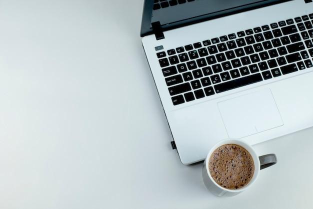 白い背景の上のココアのカップと白いラップトップ。黒のキーボードを備えたラップトップ。