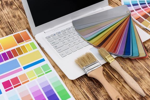 나무 테이블에 디자이너 색상 견본 흰색 노트북