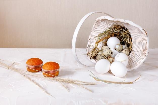 흰색 밝은 나무 테이블에 빨대가 있는 바구니에 흰색 큰 닭고기와 메추라기 알