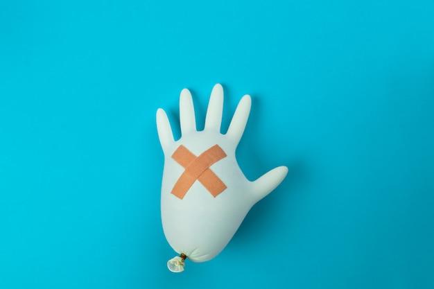 青色の背景の上に横たわる十字架の形で医療石膏で膨らませた白いラテックス手袋。薬理学の概念。