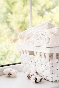 White laundry basket next to a window