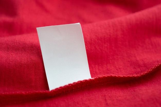 Белые инструкции по стирке белья этикетка одежды на красной хлопковой рубашке