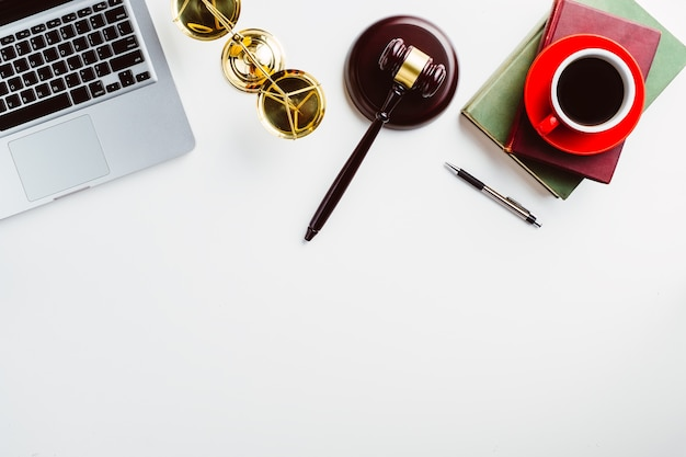 White lawyer desk with laptop, book, pen, cup of coffee, judges gavel and law symbols.
