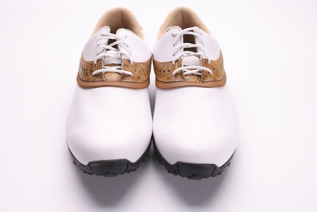 茶色のゴルフインサートが付いた白い革のブーツ