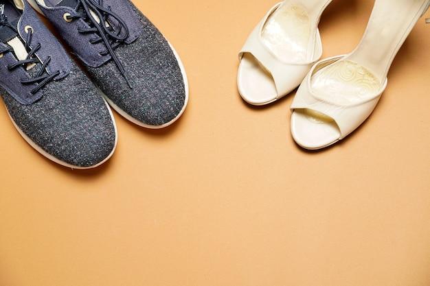 Белые кожаные деловые или вечерние женские туфли на коричневом фоне с копией пространства рядом с спортивной женской обувью. плоский вид сверху.