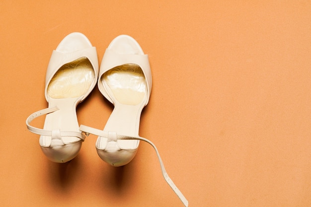 Белые кожаные деловые или вечерние женские туфли на коричневом фоне с копией пространства. плоский вид сверху.