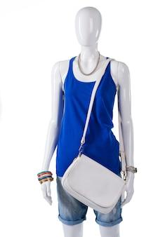 스트랩이 달린 흰색 가죽 지갑. 평범한 흰색 핸드백이 달린 마네킹. 여자 여름 의류 셀렉션. 할인과 함께 가벼운 액세서리 판매.
