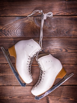 White leather skates hanging on a nail