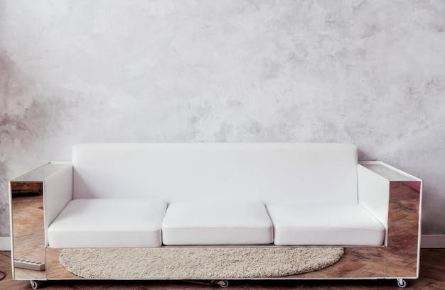 Белый кожаный диван с зеркальными рамами стоит на фоне серой бетонной стены. горизонтальное фото