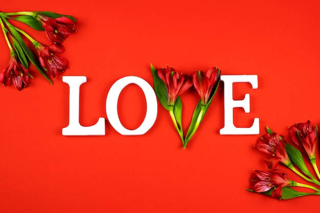 White letters love on a red wall with alstroemeria flowers. valentine's day