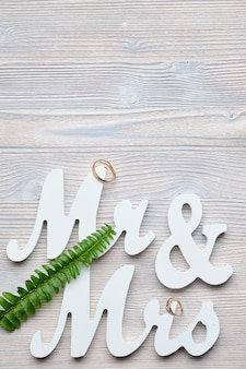 White letters mr and vhk on a wooden space with a ring and a green branch. top view. copy place.