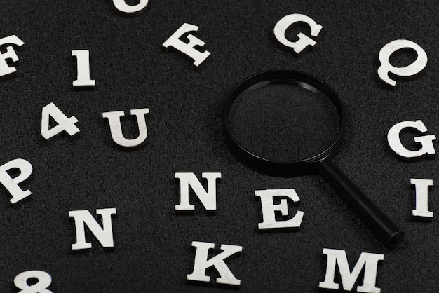White letters and numbers and magnifying glass on black background. search concept