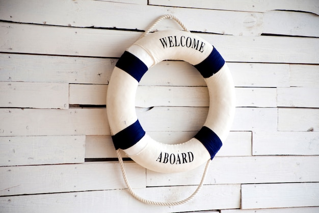 White life buoy with welcome aboard on white wall